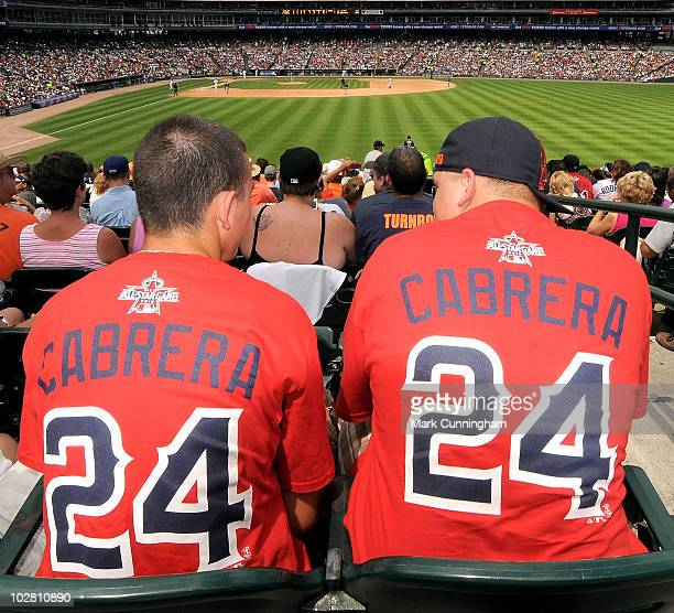 Two Miguel Cabrera of the Detroit Tigers fans sit in the outfield wearing their 2010 AllStar Game replica jerseys during the game against the...