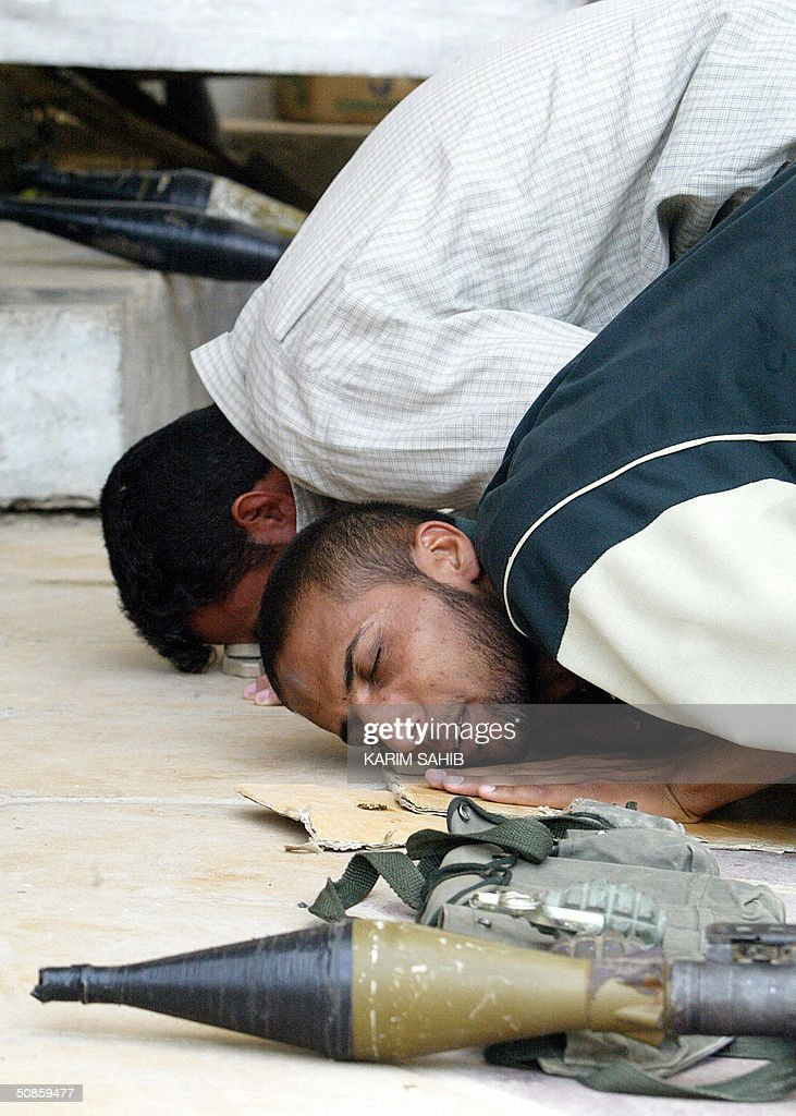 Two militiamen loyal to radical Shiite cleric Moqtada Sadr pray near their weapons 20 May 2004 as they secure the area of the Imam Hussein shrine in Karbala, 110 kms south of Baghdad. Nine civilians were killed and 16 others wounded overnight in Karbala during continuous clashes between US forces and Sadr's Army of Mehdi militia. AFP PHOTO/Karim SAHIB
