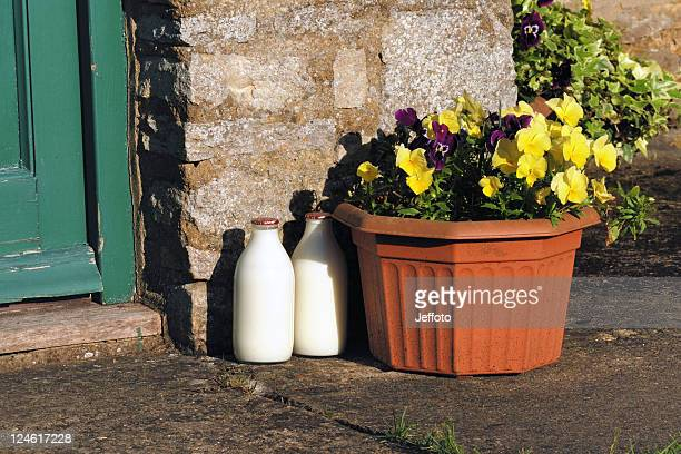 Two milk bottles in morning sun by a doorstep