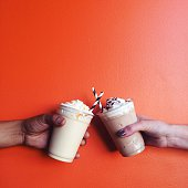 Two milkshakes isolated on orange background