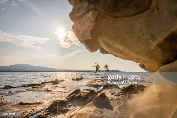 Deux soeurs Millenial sautant sur Wilderness Beach près de Formations de grès