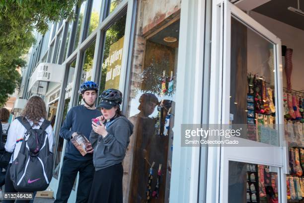 Two Millennial age cyclists wearing helmets stand outside a store on Bridgeway road in downtown Sausalito California June 29 2017