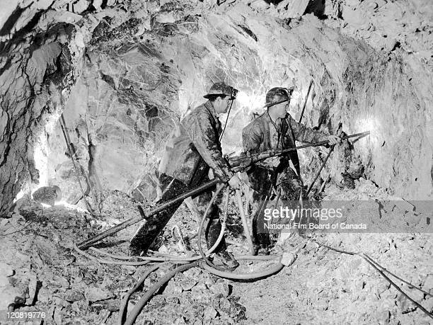 Two miners are at work drilling the asbestos ore inside an underground mine Thetford Mines Quebec Canada 1958 Photo taken during the National Film...