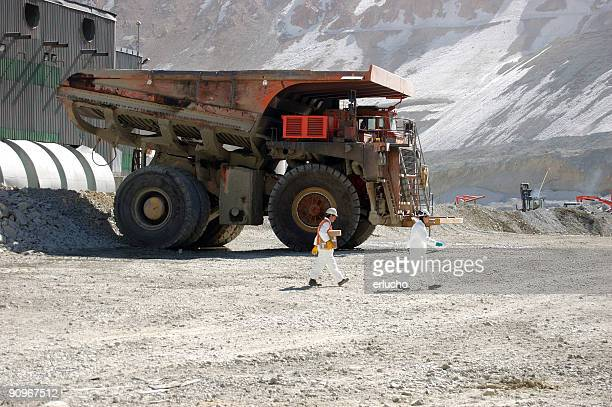 Two miners in white hard hats walk past large mining truck