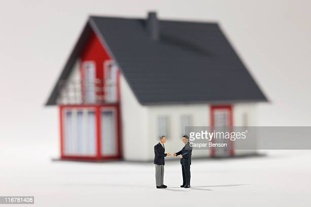 Two miniature businessmen figurines shaking hands in front of a house
