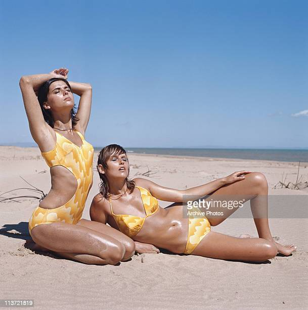 Two model wearing matching yellow swimwear on the beach 1970