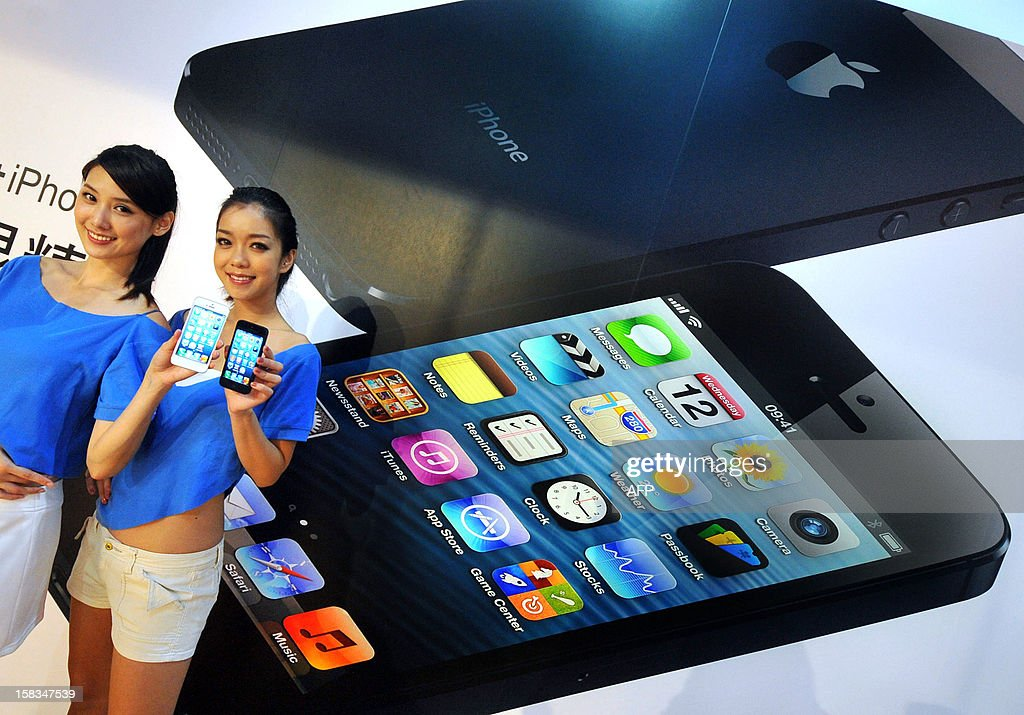 Two models display the Apple iPhone 5 during the product's release at a store in Taipei on December 14, 2012. Three main telecom companies released the lastest Apple iPhone 5 on December 14.AFP PHOTO / Mandy CHENG