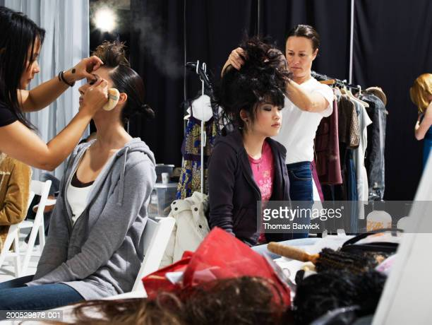 Two models having hair styled and make-up applied by stylists