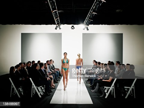 Two models in swimsuits walking down catwalk : Stock Photo