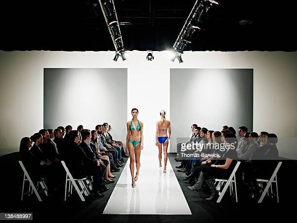 Two models in swimsuits walking down catwalk