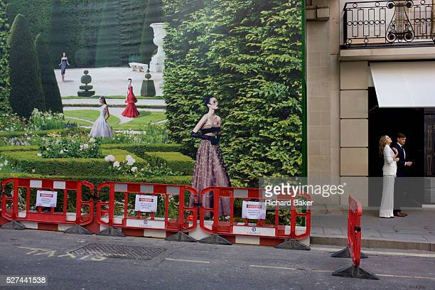 Two models on a street shoot with the background of hanging hoarding media of a Dior shop being refurbished in central London Pausing during being...