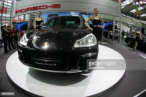 Two models perform beside a Porsche Cayenne Turbo S sports car at the Xian International Auto Expo in Qujiang International Conference Exhibition...