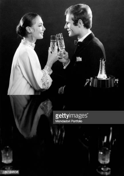 Two models smiling at each other and drinking a toast 1960s