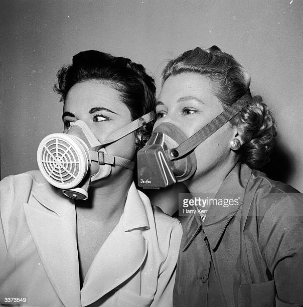 Two models wear filter masks designed to be more flattering to the female form on display at an exhibition in London