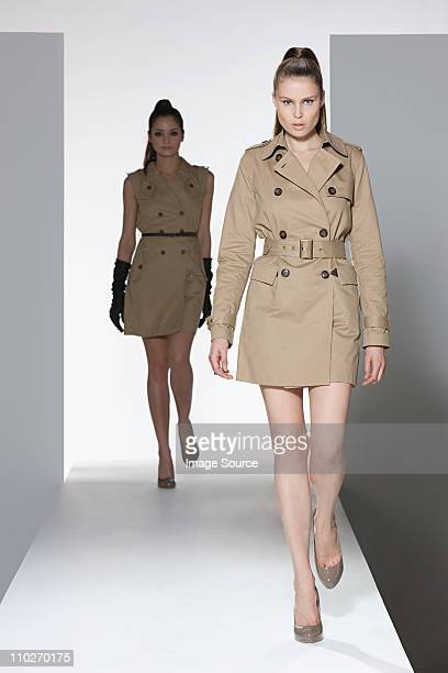 Two models wearing beige dress and mackintosh on catwalk at fashion show