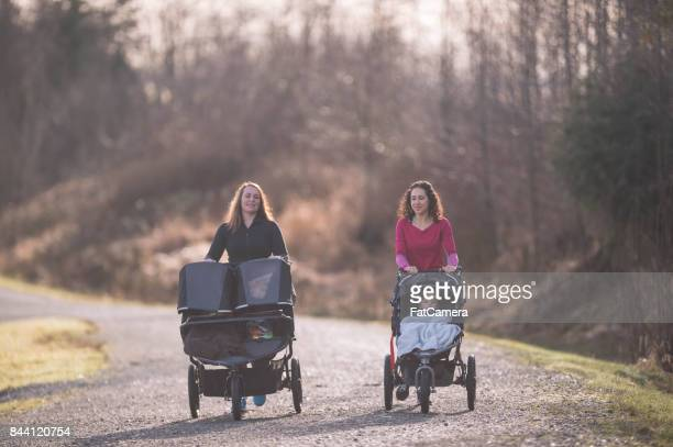 Two moms pushing children in strollers
