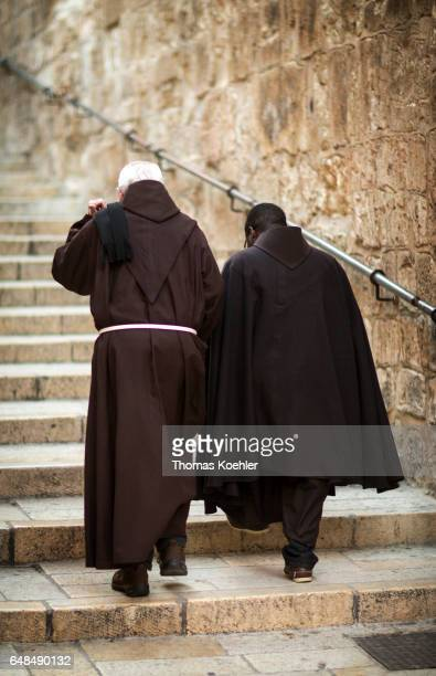 Two monks in cowls go upstairs in front of the Church of the Holy Sepulchre historic city center of Jerusalem on February 08 2017 in Jerusalem Israel
