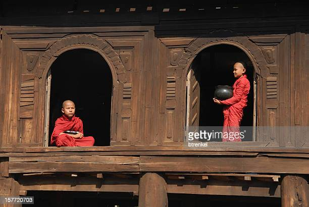 Two monks standing in 2 windows