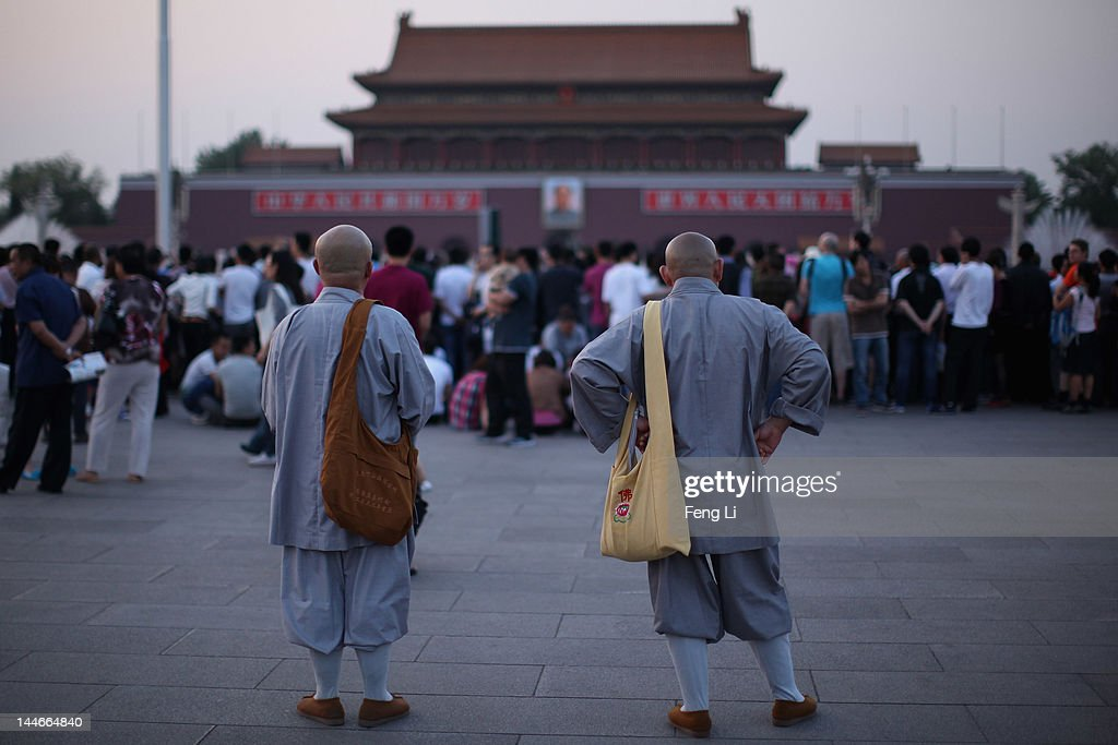 Two monks waits before the customary ceremony of lowering flag at Tiananmen Square on May 17, 2012 in Beijing, China.