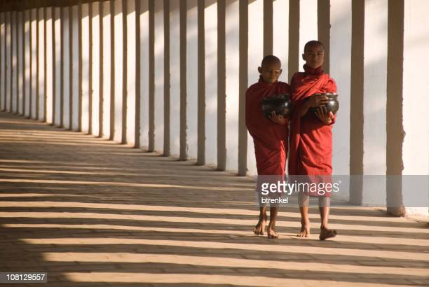 Two monks walking down a temple hallway