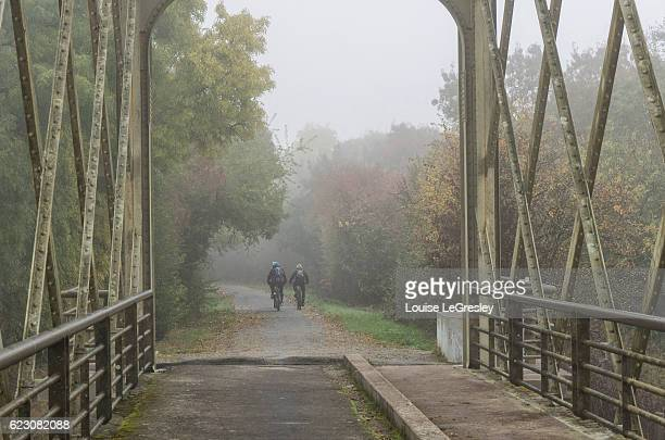 Two montain bikers crossing an old steel footbridge on a foggy morning