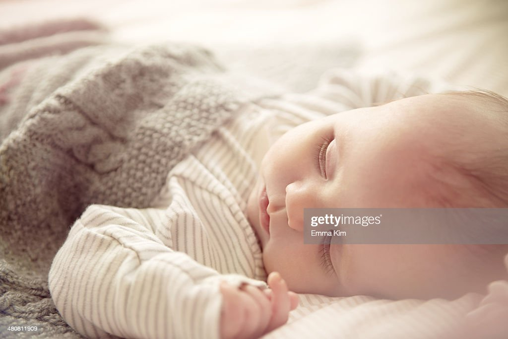 Two month old baby boy asleep in crib