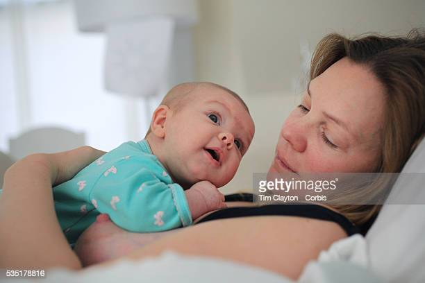 A two month old baby girl rests in bed with her mother while observing her environment Photo Tim Clayton