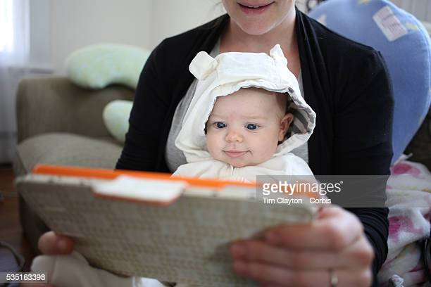 A two month old baby girl watches an interactive app for babies on an iPad while held by her mother Photo Tim Clayton
