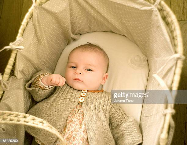 Two month old baby in basket looking to camera