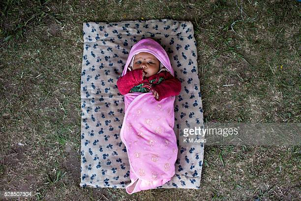 KATHMANDU BAKTOPUR KATHMANDU NEPAL A two month old little baby in the sun light in a Park area in the city center being used for overnight sleeping...