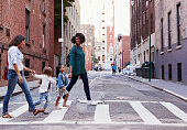 Two mother friends with two daughters crossing the road