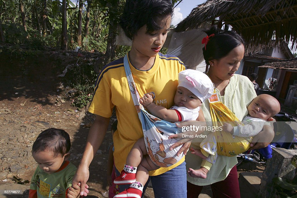 Two mothers carry their children to get polio vaccination drops May 9, 2005 at Girijaya village, Sukabumi, Indonesia. Indonesian health authorities confirmed on May 6 that at least four cases of polio with some 15 cases of acute flaccid paralysis have been diagnosed in the West Java province. All cases were found in villages of the Sukabumi district, about 100 kilometres (62 miles) south of Jakarta. An epidemic of polio in Indonesia has broken out after ten years of being free of the disease. Indonesia is the 16th previously polio-free country to be reinfected in the past two years, including 13 in Africa, according to the United Nations health agency.