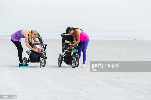 Two mothers helping their babies in strollers