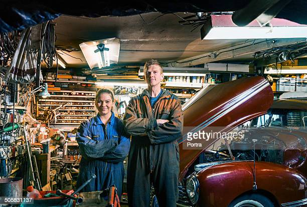 Two motor mechanics standing in their work shop.