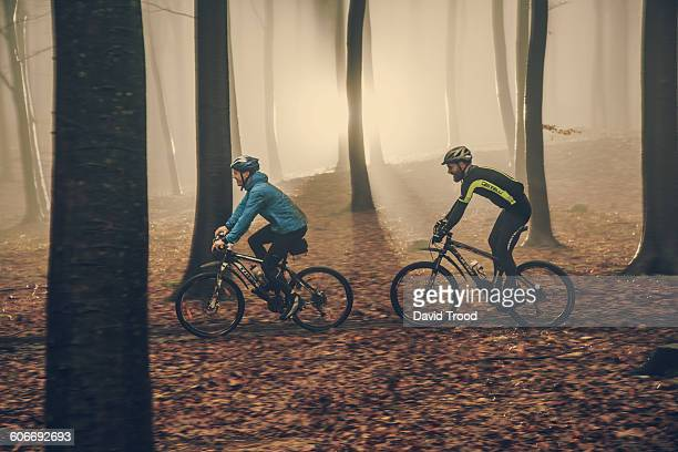 Two mountain bikers in misty forest