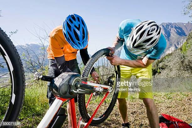 Two Mountainbikers repairing flat type on E-bike