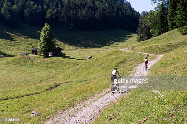 Two mountainbking girls on a flat gravel road on a summery open alpine country side in the region Wilder Kaiser in Austria