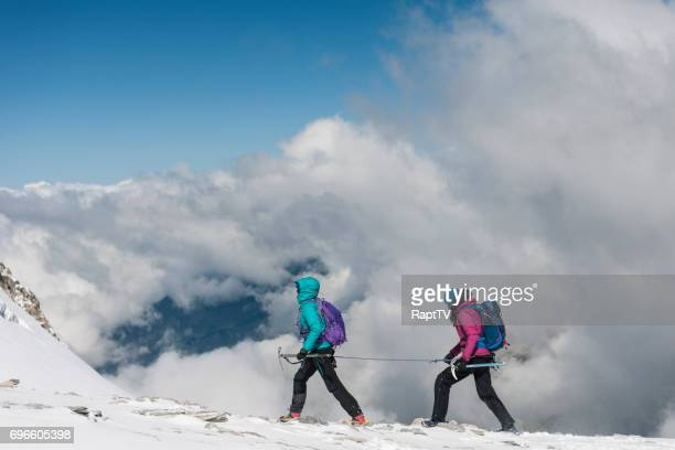 Two mountaineers grossing a glacier above the Clouds.
