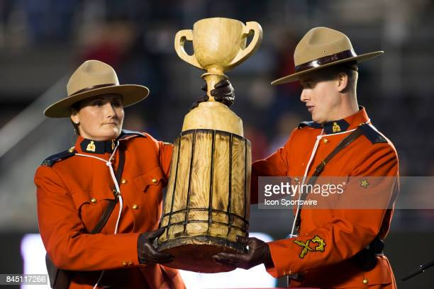 Two Mounties from the Royal Canadian Mounted Police guard a chainsaw carving of Lord Grey's Cup that was given at halftime to Henry 'Hank' Burris to...
