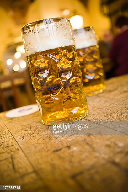 Two mugs of beer on a pub table.