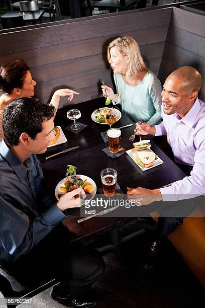 Two multiethnic couples eating in restaurant