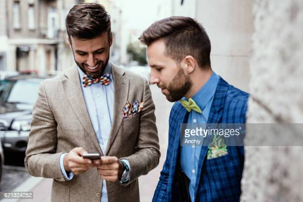 Two multi-ethnic fashion critics check for the location of the fashion show that they will attend together.