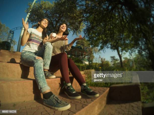 Two multiethnic girls sitting together on steps in park.