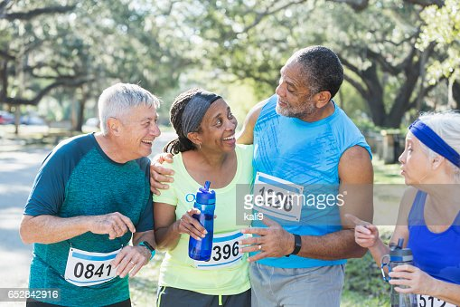 Two multi-ethnic senior couples at end of race : Stock Photo