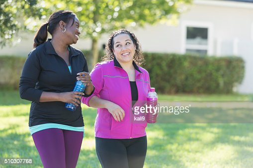 Two multi-ethnic women drinking sports drinks outdoors