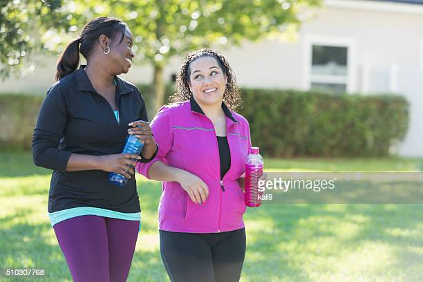 Due multi-etnico donne bere bevande sportive all'aperto