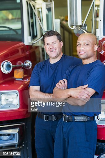 Two multiracial firemen with fire engines at the station