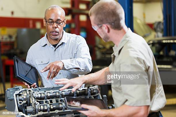 Two multi-racial mechanics with digital tablets, talking