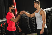 Respect in sport. Two muscular men are making fist bump gesture during workout in the gym.