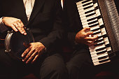 Hands of percussionist and accordionist with instruments.